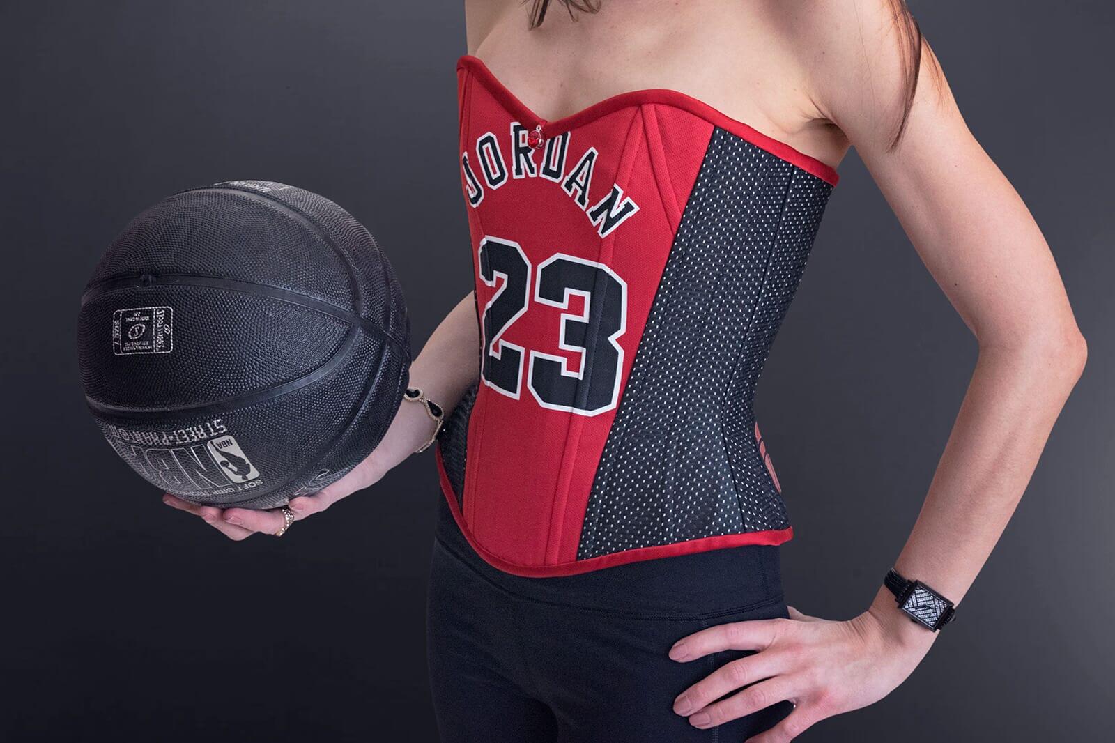 Stella holding basketball wearing her Chicago Bulls Michael Jordan Corset #23 on black background
